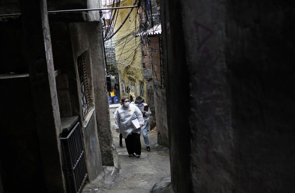 """Health workers walk through the Rocinha slum to test people for COVID-19 and set up future appointments as part of a rapid test campaign by the civilian organization """"Bora Testar,"""" or """"Let's Test"""" in Rio de Janeiro, Brazil, Thursday, Oct. 8, 2020. Financed by crowdfunding and donations, the organization aims to test up to 300 people in the slum. (AP Photo/Silvia Izquierdo)"""