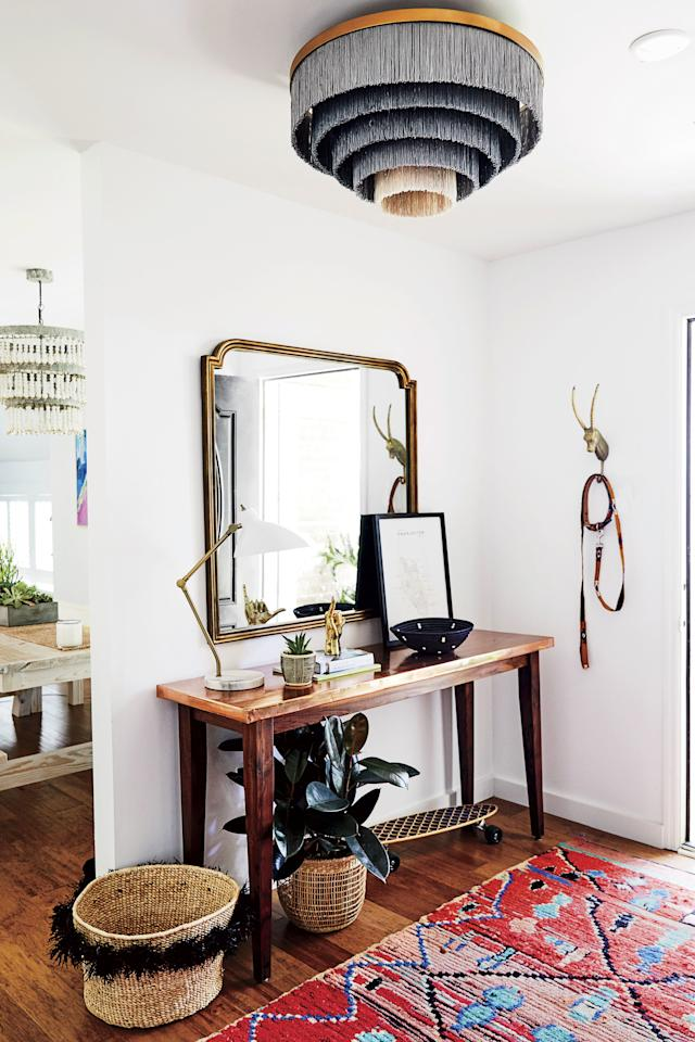 """<p>""""The entry needed to set the tone for the entire place but also be functional. Handwoven baskets are catchalls for keys, shoes, and packages, and the brass gazelle head is where I hang my dog's leash. The walnut-and-copper console was built by <a href=""""https://www.greenwoodmilling.com/"""">Green Wood Milling Company</a> in San Antonio. The wood came from a walnut tree that fell during a tornado in Texas. It's an heirloom-quality piece I'll keep forever.""""</p>"""