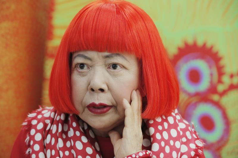 In this photo taken Wednesday, Aug. 1, 2012, Japanese avant-garde artist Yayoi Kusama, wearing a bright red wig and a Louis Vuitton polka dot scarf, speaks during an interview at her studio in Tokyo. Kusama's signature splash of dots has now arrived in the realm of fashion in a new collection from French luxury brand Louis Vuitton - bags, sunglasses, shoes and coats. The latest Kusama collection is showcased at its boutiques around the world, including New York, Paris, Tokyo and Singapore, sometimes with replica dolls of Kusama. (AP Photo/Itsuo Inouye)