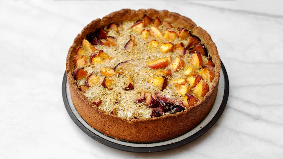 """This luscious sunset of tart from Epi contributor Tara O'Brady has an easy press-in pistachio crust and a few pounds of peaches, plums, or apricots coddled in a supple layer of custard. <a href=""""https://www.epicurious.com/recipes/food/views/stone-fruit-custard-tart?mbid=synd_yahoo_rss"""" rel=""""nofollow noopener"""" target=""""_blank"""" data-ylk=""""slk:See recipe."""" class=""""link rapid-noclick-resp"""">See recipe.</a>"""