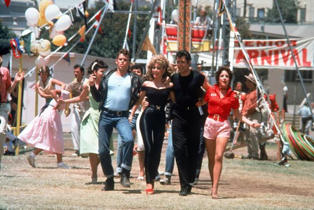 Jeff Conaway (Kenickie), Olivia Newton-John (Sandy), John Travolta (Danny), and Stockard Channing (Rizzo) in the <em>Grease</em> carnival scene, with Jamie Donnelly (Jan) at left in the green dress. (Photo: Paramount Pictures/courtesy of the Everett Collection)