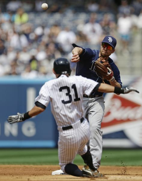 Tampa Bay Rays second baseman Ben Zobrist throws out New York Yankees' Robinson Cano at first base after forcing out Yankees' Ichiro Suzuki (31), of Japan, during the fourth inning of a baseball game Saturday, July 27, 2013, in New York. (AP Photo/Frank Franklin II)
