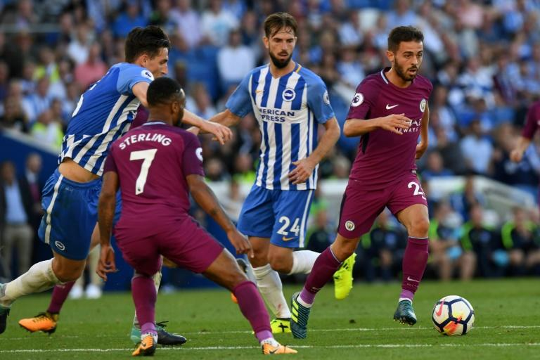 Manchester City's Bernardo Silva (R) runs with the ball during their English Premier League match against Brighton & Hove Albion, at the American Express Community Stadium in Brighton, on August 12, 2017