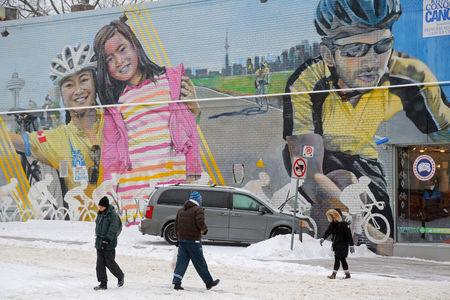 Commuters pass by a mural outside a sporting goods shop during a snowstorm in Toronto