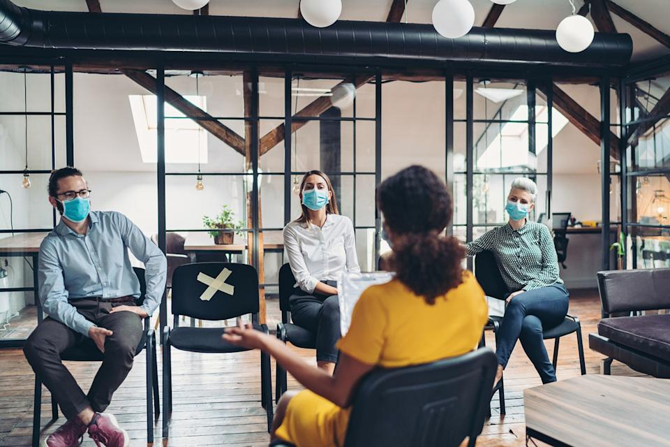 A group of coworkers wearing face masks sit in an office and have a meeting while social distancing.