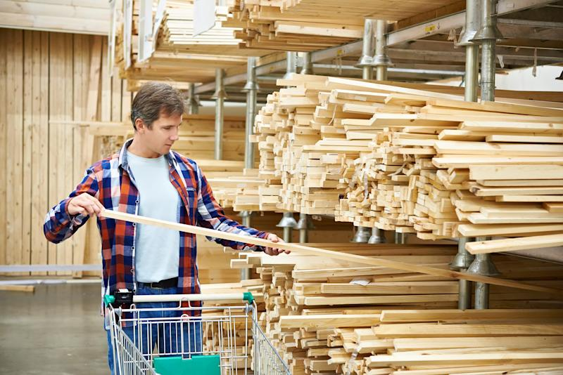 A customer selects a piece of lumber from store shelves