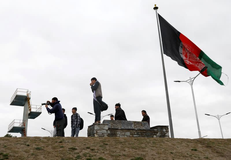 FILE PHOTO: Youths take pictures next to Afghan flag in Kabul