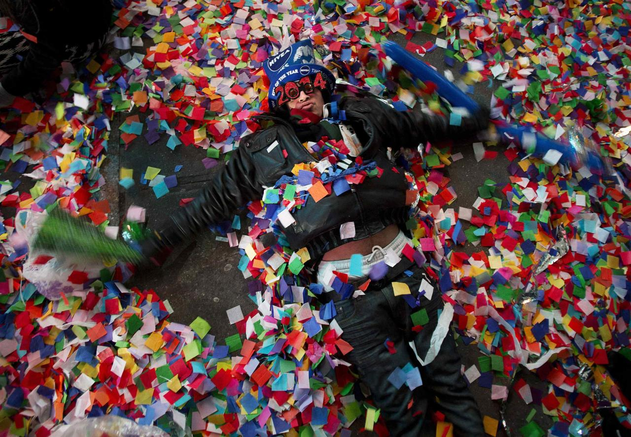 A reveler makes angels in the confetti on the ground during New Year's Eve celebrations in Times Square in New York, January 1, 2014. REUTERS/Carlo Allegri (UNITED STATES - Tags: SOCIETY ANNIVERSARY)