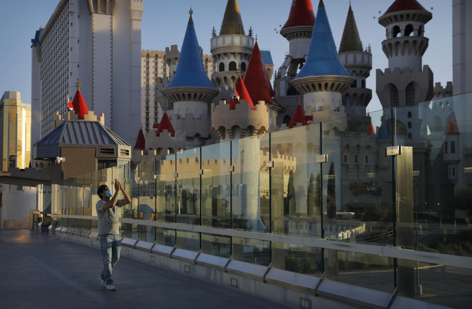 In this April 18, 2020, photo, a man wearing a mask as a precaution against the coronavirus takes pictures along the Las Vegas Strip in Las Vegas. (AP Photo/John Locher)