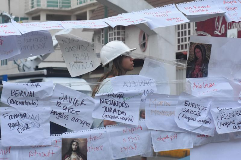 A woman is seen reading letters written to rememberchildren who have died during the earthquake.