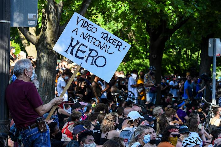 """<i>Protesters gather outside the residence of Minnesota Gov. Tim Walz on June 1. One man's sign reads: """"Video taker: A national hero.""""</i>"""