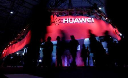 Visitors walk past Huawei's booth during Mobile World Congress in Barcelona, Spain, February 27, 2017. REUTERS/Eric Gaillard/Files