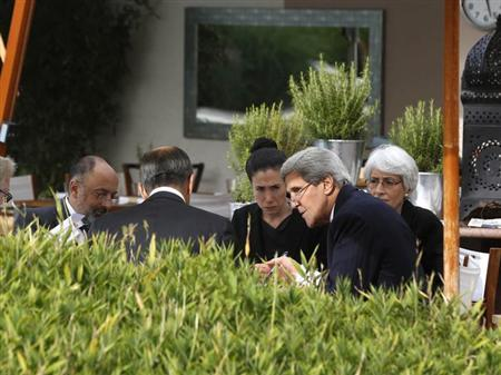 U.S. Secretary of State John Kerry (2nd R) and Russian Foreign Minister Sergei Lavrov (back to camera) negotiate ongoing problems in Syria, while seated with their senior aides by the swimming pool at a hotel in Geneva September 14, 2013. REUTERS/Larry Downing