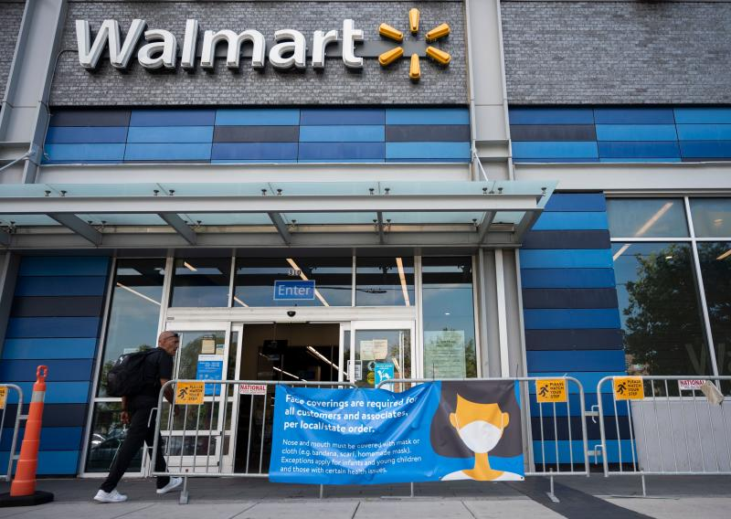 A man walks near a sign informing customers that face coverings are required in front of a Walmart store in Washington, DC on July 15, 2020. - Walmart will require shoppers to wear face masks starting next week, the US retail giant announced on July 15, joining an increasing number of businesses in mandating the protection amid the latest spike in coronavirus cases. (Photo by ANDREW CABALLERO-REYNOLDS / AFP) (Photo by ANDREW CABALLERO-REYNOLDS/AFP via Getty Images)