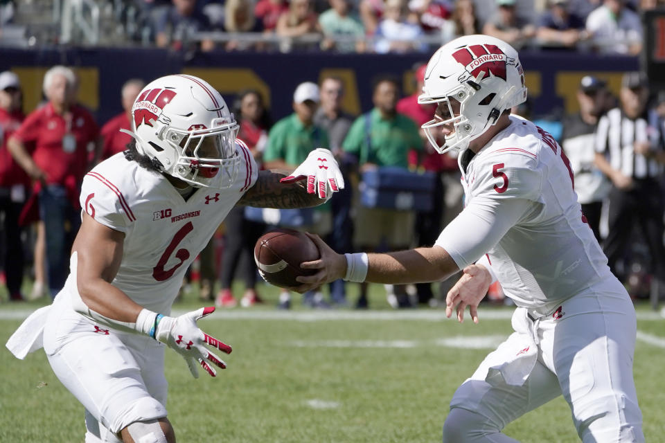 Wisconsin quarterback Graham Mertz (5) hands off to Chez Mellusi during the first half of an NCAA college football game against Notre Dame Saturday, Sept. 25, 2021, in Chicago. (AP Photo/Charles Rex Arbogast)