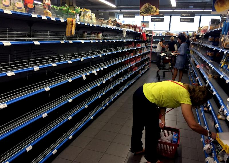 Shoppers stand in an aisle with empty shelves in a supermarket in Athens on July 4, 2015 (AFP Photo/Aris Messinis)
