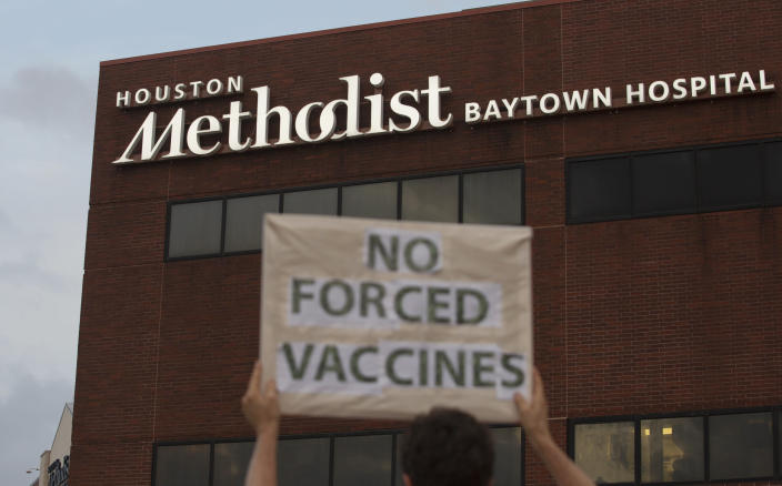 People bring signs to protest Houston Methodist Hospital system's rule of firing any employee who is not immunized by Monday, June 7, 2021, at Houston Methodist Baytown Hospital in Baytown, Texas. Houston Methodist staff who have refused the COVID-19 vaccine so far and their supporters participated in a gathering and march. (Yi-Chin Lee/Houston Chronicle via AP)
