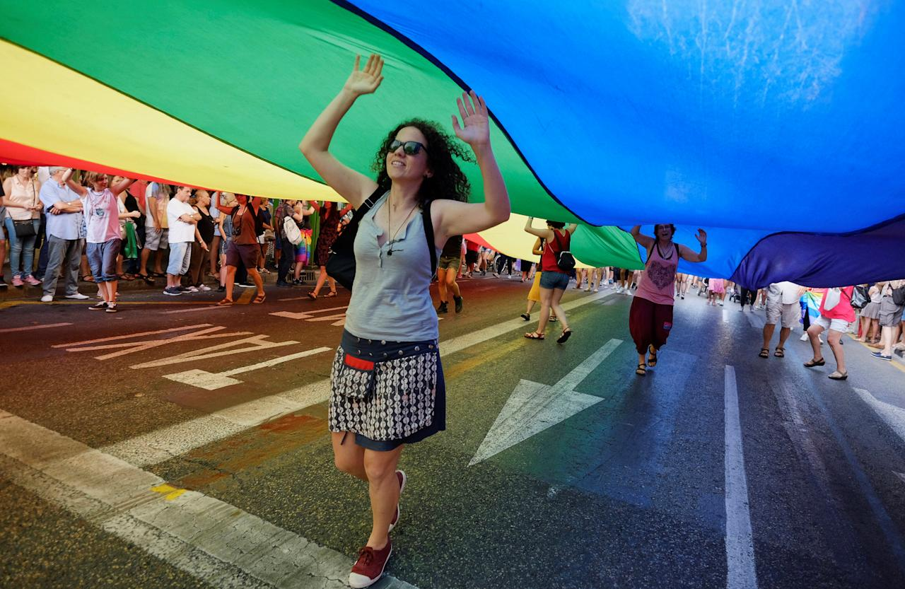 People dance under a giant LGBT flag during the LGBT Pride Parade in Valencia, Spain, June 24, 2017. REUTERS/Heino Kalis