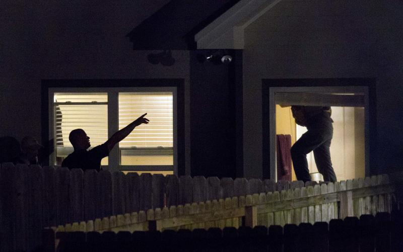 Law enforcement officials search a home in Montgomery, Ala., Monday, June 11, 2012.  Authorities searching for the man charged with fatally shooting three people near Auburn University swarmed the house Monday where they believe he's hiding, firing tear gas and sending a tactical team on cautious forays inside. (AP Photo/Dave Martin)