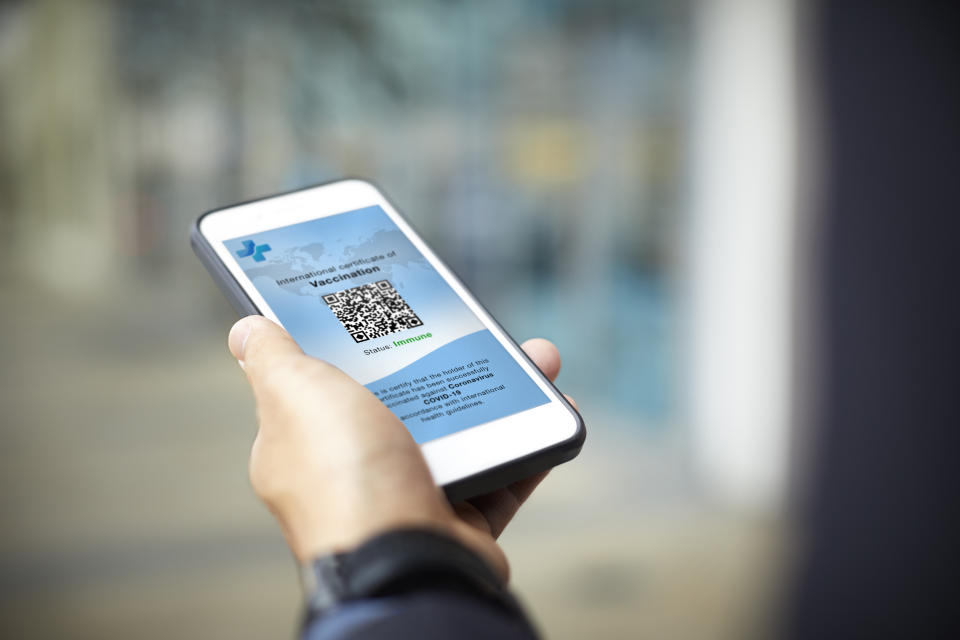 Cropped image of businessman having online Covid-19 Vaccine Passport. Male executive is using smart phone in airport. Traveling information is displayed on screen.
