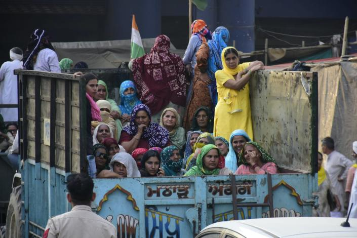 Dozens of Indian women look solemnly defiant riding in the back of a truck