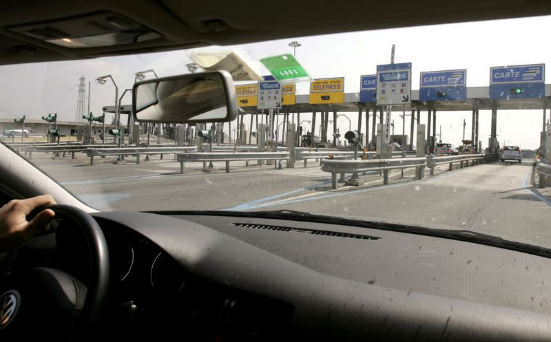 FILE PHOTO: A driver approaches an Autostrade motorway toll along a highway on the outskirts of Rome April 24, 2..