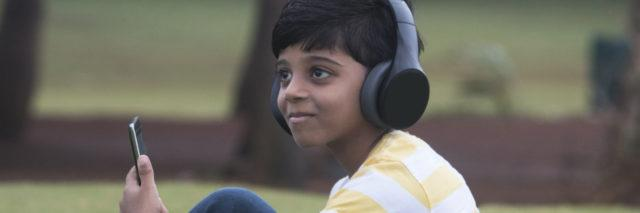 Boy with headphones and tablet at park.