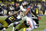 Ohio State's Dontre Wilson (1) is stopped by Michigan' Dennis Norfleet (23) on a punt return during the second quarter of an NCAA college football game in Ann Arbor, Mich., Saturday, Nov. 30, 2013. (AP Photo/Carlos Osorio)
