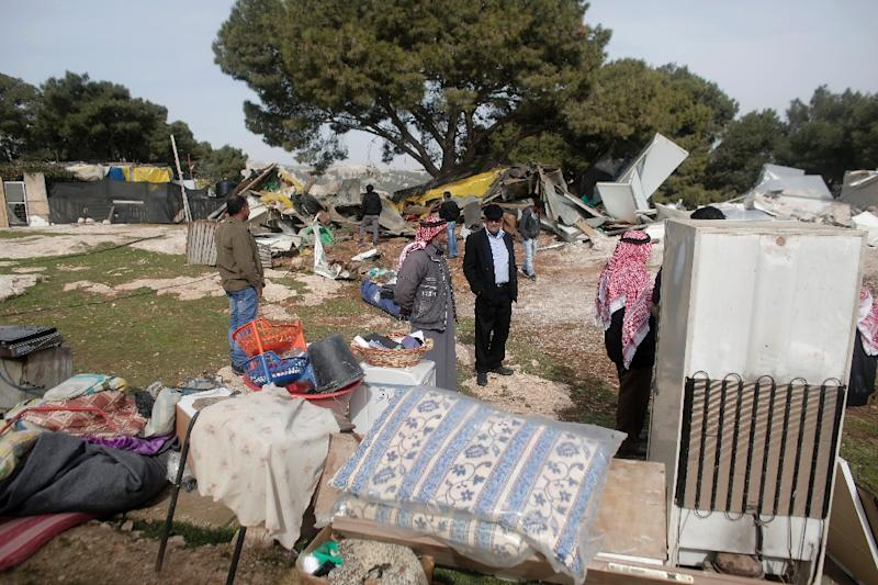 Palestinian Bedouins inspect the remains of makeshift homes that were demolished by the Israeli army in the West Bank city of al-Azariya, on January 21, 2016 (AFP Photo/Ahmad Gharabli)
