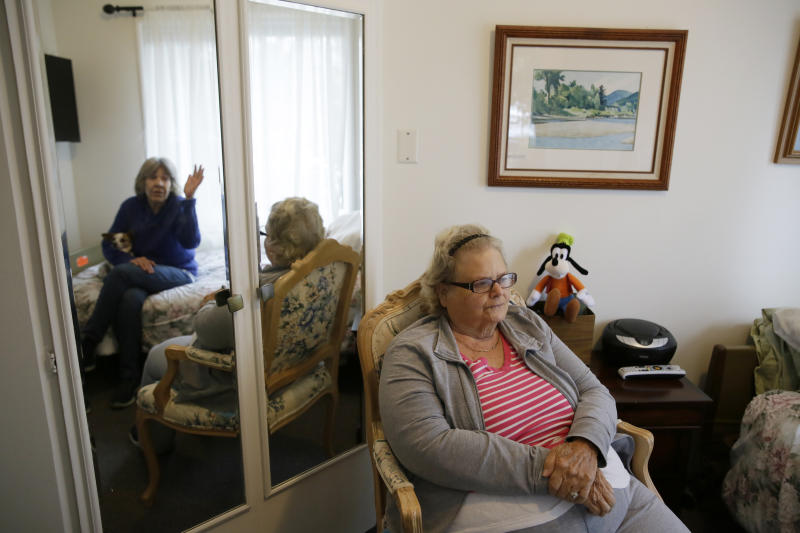 In this photo taken Thursday, Dec. 5, 2019, Rosalie Harris, 80, right, sits in her room and talks with her sister, Marcey Smith, left in mirror, who was visiting at the Cedars Care Home in Calistoga, Calif.  Even before widespread blackouts hit California this fall, the utility that triggered them showed signs it wasn't fully prepared. An Associated Press review reveals persistent problems during four smaller shutoffs that Pacific Gas & Electric did starting last year so power lines downed by strong winds wouldn't spark wildfires.  (AP Photo/Eric Risberg)