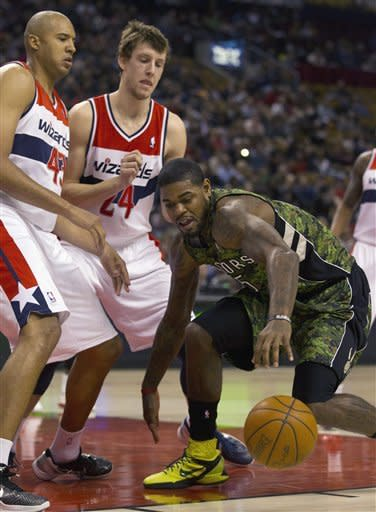Toronto Raptors forward Amir Johnson, right, gathers up the loose ball against Washington Wizards forwards Brian Cook (43) and Jan Vesely (24) during first half NBA action in Toronto on Sunday April 1, 2012. (AP Photo/The Canadian Press, Frank Gunn)