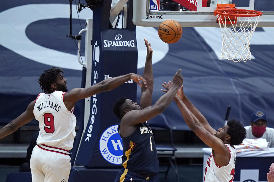 New Orleans Pelicans forward Zion Williamson (1) goes to the basket between Chicago Bulls forward Patrick Williams (9) and forward Thaddeus Young (21) during the second half of an NBA basketball game in New Orleans, Wednesday, March 3, 2021. (AP Photo/Gerald Herbert)