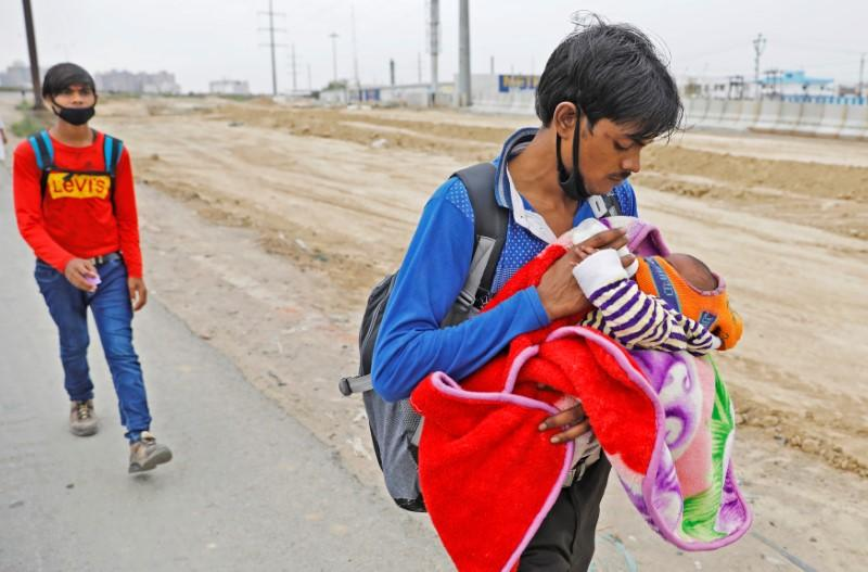 A migrant worker feeds his newborn baby as he walks on a highway looking out for a transport to return to his village, after India ordered a 21-day nationwide lockdown to limit the spreading of coronavirus disease (COVID-19), in Ghaziabad