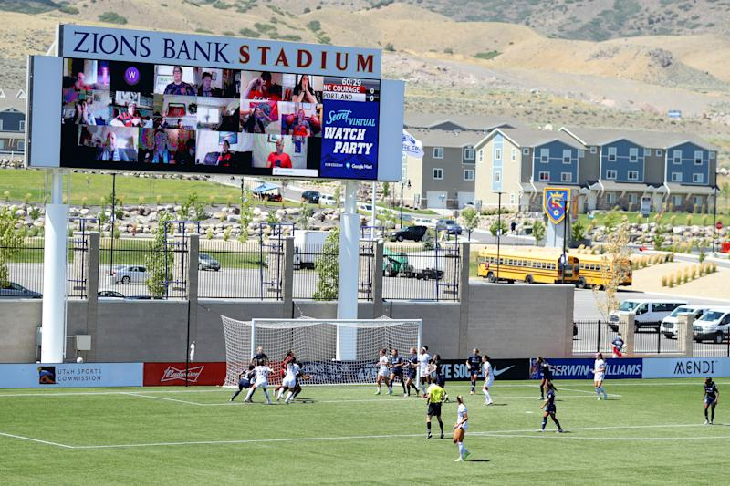 Fans are shown on a big screen behind the net at Zions Bank Stadium.