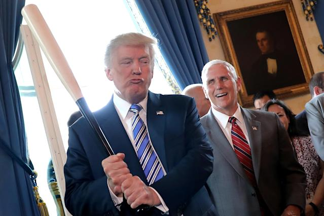 Vice President Mike Pence laughs as President Donald Trump holds a baseball bat at a Made in America product showcase event at the White House on July 17, 2017. (REUTERS/Carlos Barria)