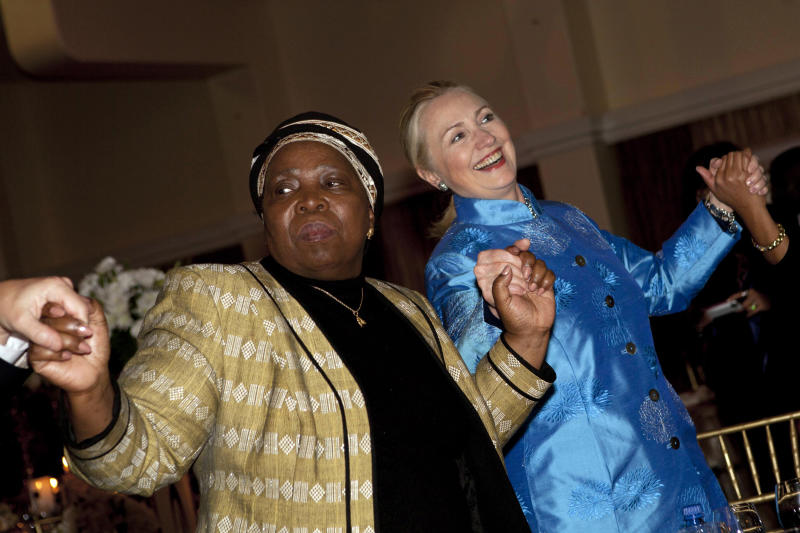 FILE - In this Aug. 7, 2012 file photo, Secretary of State Hillary Rodham Clinton holds hands during a dance with other officials including African Union Chair-Designate Nkosazana Dlamini-Zuma, during a gala dinner at Sefako M. Makgatho Presidential Guest House in Pretoria, South Africa. On an epic safari through Africa, U.S. Secretary of State Hillary Rodham Clinton braved Uganda's Ebola outbreak, dealt with a swarm of angry Malawian bees, endured a rare South African snowstorm and shimmied on a dance floor in South Africa, earning the nickname the Secretary of Shake. And as she wrapped up her nine-nation African tour on Friday in Benin,Clinton shattered her own already herculean travel record. (AP Photo/Jacquelyn Martin, File, Pool)