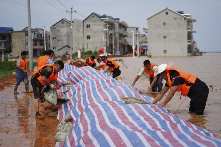 In this photo released by Xinhua News Agency, workers build a dyke to stop flood waters at Jiangjialing village of Poyang County in eastern China's Jiangxi province Saturday, July 11, 2020. Chinese authorities forecasted heavy rain across a wide swath of the country prompting evacuation of residents and raising emergency alerts levels. (Zhang Haobo/Xinhua via AP)