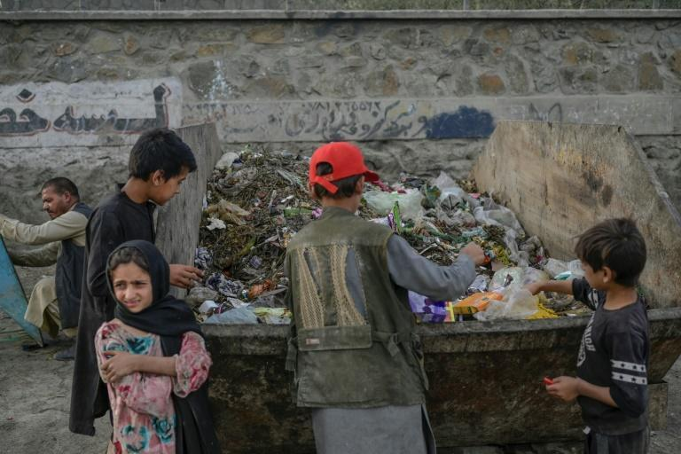Children collect food and recyclables from a waste container near Kabul airport on September 21, 2021 (AFP/BULENT KILIC)