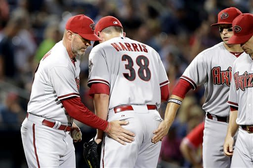 Arizona Diamondbacks relief pitcher Will Harris, center, is relieved by manager Kirk Gibson, left, in the seventh inning of a baseball game against the Atlanta Braves, Friday, June 28, 2013, in Atlanta. (AP Photo/David Goldman)