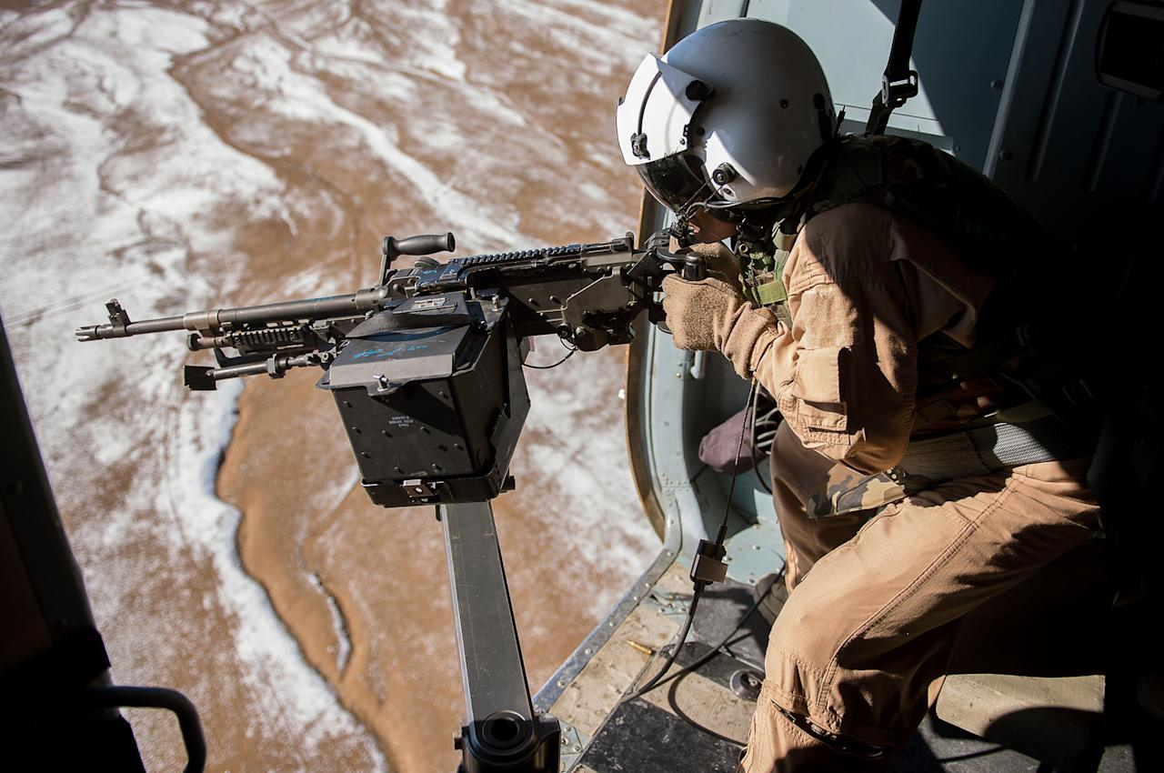 "Afghan air force Sgt. Razeg, a gunner, fires an M-240 weapon from an Mi-17 Helicopter during a mission from Kabul, Afghanistan. The flight was a ""check ride"" mission, allowing an Afghan air force copilot and gunner to further train and qualify in their respective jobs (Dennis J. Henry Jr/USAF/Rex Features)"