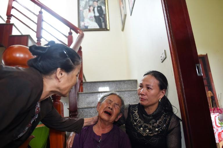 Tran Thi Hue (C), grandmother of 30-year old Le Van Ha, who is feared to be among the 39 people found dead in a truck in Britain, is consoled by relatives inside their house in Vietnam's Nghe An province (AFP Photo/NHAC NGUYEN)
