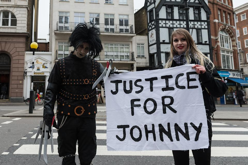 LONDON, UNITED KINGDOM - MARCH 18, 2021: Johnny Depp's supporters, one dressed as the movie character Edward Scissorhands (L), hold a banner outside the Royal Courts of Justice as Johnny Depp's legal team applies for permission to appeal, and to rely on further evidence in a bid to overturn last year's ruling in the libel claim against The Sun and its publisher News Group Newspapers over an article labelling him a wife beater, on 18 March, 2021 in London, England. The ruling by a High Court judge Mr Justice Nicol following a three-week trial in July last year found that the claims in the article were substantially true and that the US actor had assaulted his ex-wife Amber Heard. (Photo credit should read Wiktor Szymanowicz/Barcroft Media via Getty Images)