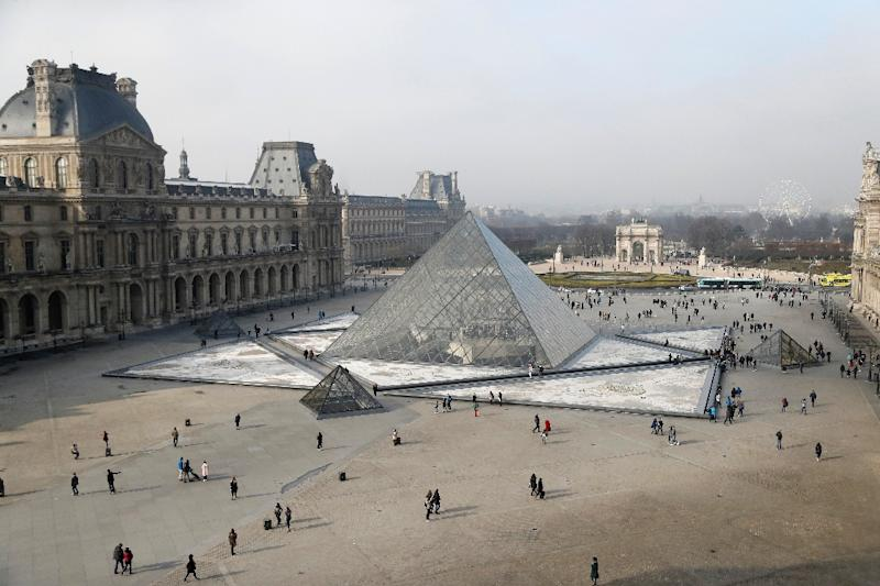 People walk around the pyramid of the Louvre in this February 18, 2017 photo (AFP Photo/FRANCOIS GUILLOT)