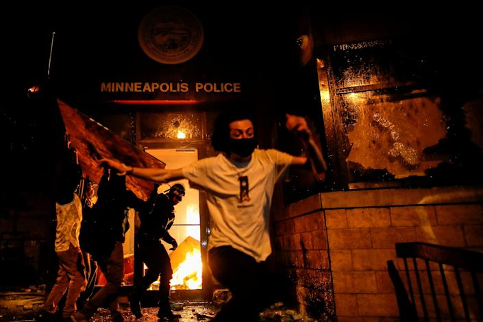 Protesters react as they set fire to the entrance of a police station as demonstrations continue in the aftermath of the death in Minneapolis police custody of George Floyd, in Minneapolis, Minnesota, U.S., May 28, 2020.