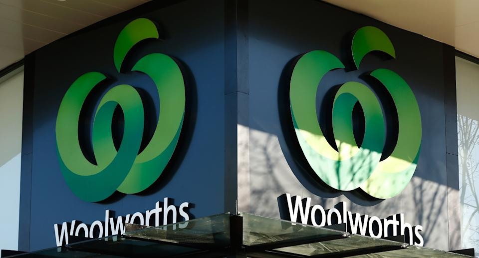 A Woolworths supermarket sign is displayed outside a shopping centre, showing the iconic green logo.
