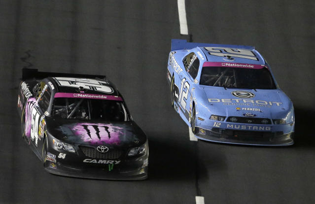Kyle Busch (54) leads Sam Hornish Jr. (12) on the front stretch during the NASCAR Nationwide Series auto race at Charlotte Motor Speedway in Concord, N.C., Friday, Oct. 11, 2013. Busch won the race. (AP Photo/Gerry Broome)