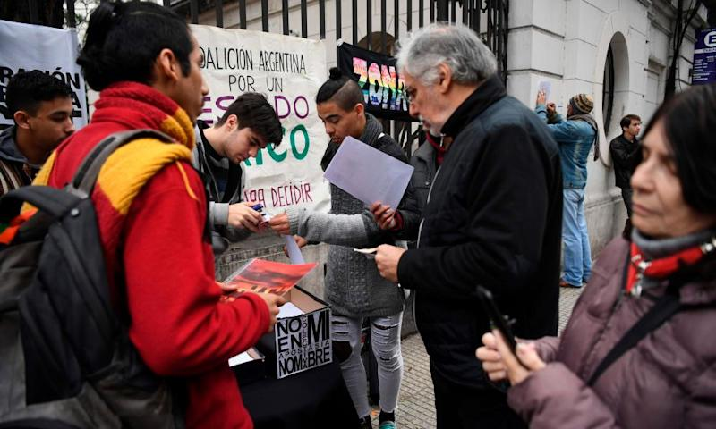 People sign forms to renounce their religious affiliation to the Catholic church outside the Argentine Episcopal Conference in Buenos Aires on 24 August, 2018.