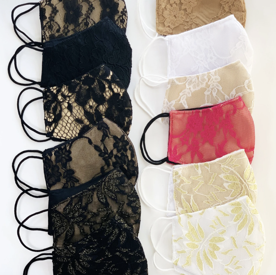12 lace face masks laying on table in several colours