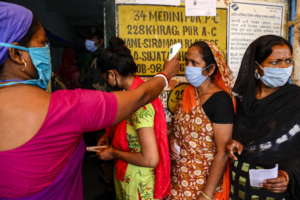 A woman takes the body temperature of a voter standing in a queue to cast her vote outside a polling booth during first phase of elections in West Bengal state in Medinipur, India, Saturday, March 27, 2021. Voting began Saturday in two key Indian states with sizeable minority Muslim populations posing a tough test for Prime Minister Narendra Modi's popularity amid a months-long farmers' protest and the economy plunging with millions of people losing jobs because of the coronavirus pandemic. (AP Photo/Bikas Das)