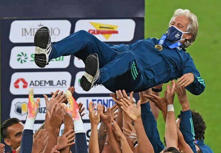 Flamengo players tossed 65-year-old coach Jorge Jesus into the air after clinching the Rio de Janeiro state title in an empty Maracana